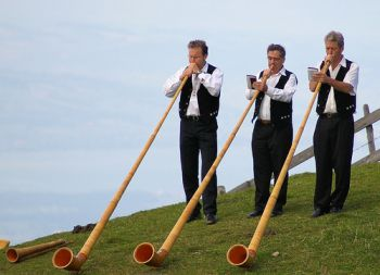 Three men playing alphorns