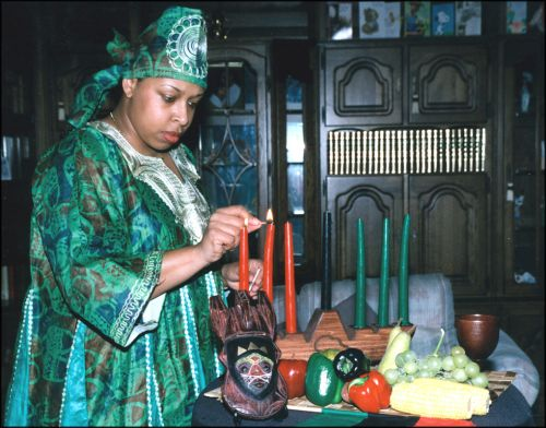 A woman lights kinara candles